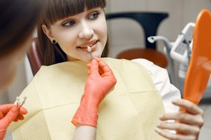 Woman in a dental chair. Girl chooses an implant. Beauty treats her teeth
