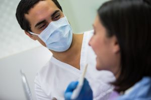 Close-up of dentist examining female patient with model of teeth shades